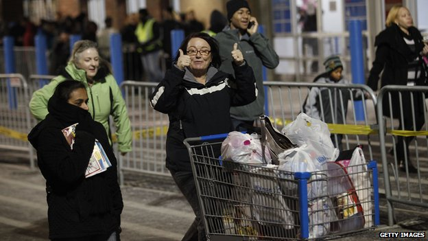 A customer gives the thumbs-up as she leaves with her purchased items outside Wal-Mart Thanksgiving day on November 28, 2013 in Troy, Michigan