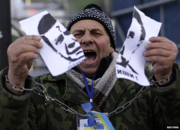 A protester in Kiev, with symbolically chained hands, rips up a picture of Ukrainian President Viktor Yanukovych, 29 November