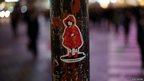 A sticker art made by an artist known as 281 Antinuke is seen on a traffic light on a street in Tokyo