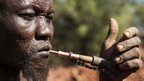 A man in smoking a pipe in Eastern Equatoria in South Sudan - Thursday 28 November 2013