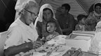 A Belgian doctor prescribes medicine to a newly-displaced woman's child at Wadi Dleil, a temporary tent camp set up in Jordan in 1967