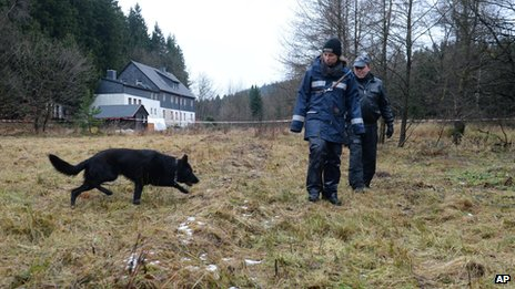 Police with a sniffing dog investigate the area around a house near Reichenau, eastern Germany Friday Nov. 29, 2013