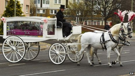 Jasmine Allsop's pink coffin in a white carriage drawn by two white horses with pink plumes in their manes