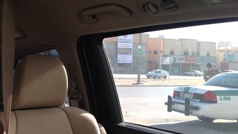 A Saudi police car parked close to the vehicle that Aziza al Yousef has been driving