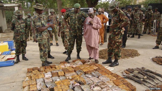 Military officials stand near ammunitions seized from suspected members of Hezbollah after a raid of a building in Nigeria's northern city of Kano May 30, 2013