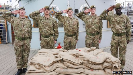 Five soldiers salute as they stand guard over bags of soil collected from Belgium's WW1 battlefields on board a navy ship