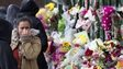 A woman reacts as she looks at floral tributes left at the scene where Lee Rigby was killed