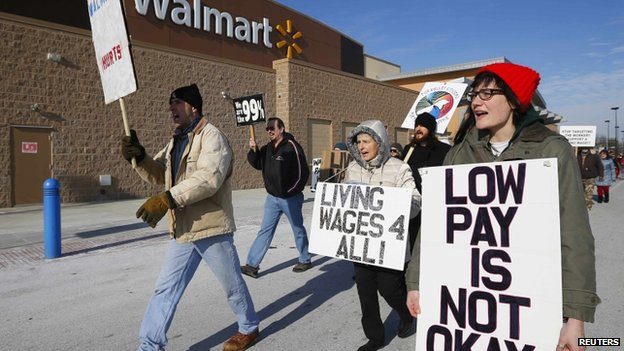 A group of protesters walk through the Walmart retail store parking lot on Black Friday in Elgin, Illinois, ON 29 November 2013