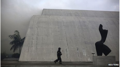 Fire fighter walks past Latin America Memorial building in Sao Paulo, Brazil