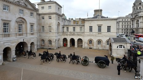 A gun carriage carrying bags of sacred soil is processed through Horse Guards Parade
