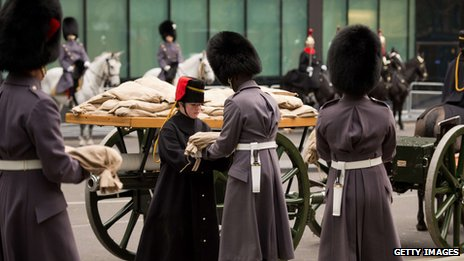 "A member of the Household Cavalry Mounted Regiment receives a sandbag of ""sacred soil"" from First World War battlefields, ahead of the ceremonial procession to transport it to the site of the Flanders Fields memorial garden in Wellington barracks,"