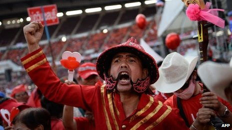 A Thai pro-government Red Shirt supporter in traditional costume shouts slogans