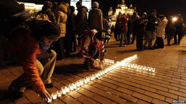 Protesters put candles in front of St Michael's golden-domed cathedral in Kiev