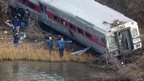 Emergency workers examine the site of a Metro-North train derailment in the Bronx borough of New York