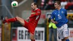 Cliftonville defender Ronan Scannell gets to the ball before Linfield forward Mark McAllister at Solitude