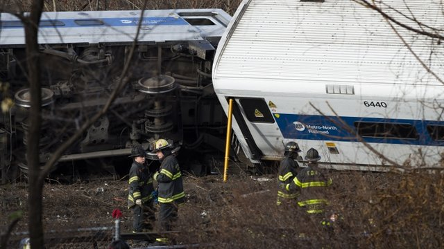 Fire fighters beside upturned Metro North Railroad train carriages