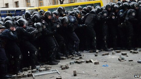 Police brace as they are pelted with paving stones