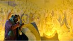 A woman checks her make-up as she stands in front of a fresco inside St Michael Cathedral.