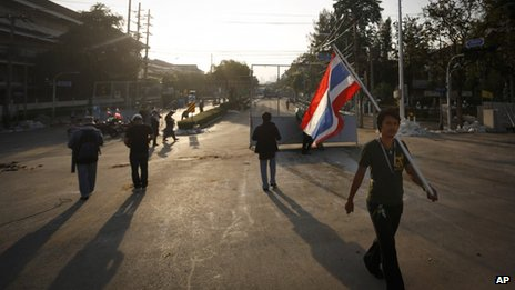 An anti-government protester walks with a Thai national flag near the compound of  the Thai Prime Minister's office in Bangkok, Thailand, 2 December 2013