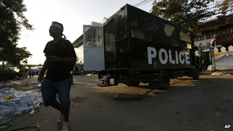 An anti-government protester walks next to a destroyed police truck near the compound of the Thai Prime Minister's office in Bangkok, Thailand, 2 December, 2013