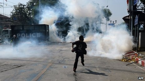 An anti-government protester runs as police fire tear gas shells at them outside the Government house during a demonstration in Bangkok on 2 December 2013