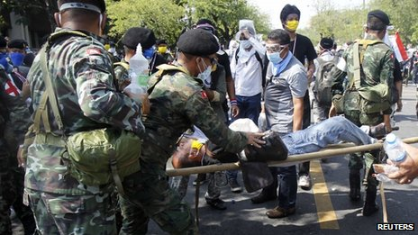 A military medical unit team assists an injured protester after riot policemen threw a teargas canister during clashes with the police near the metropolitan police headquarters in Bangkok, 2 December 2013