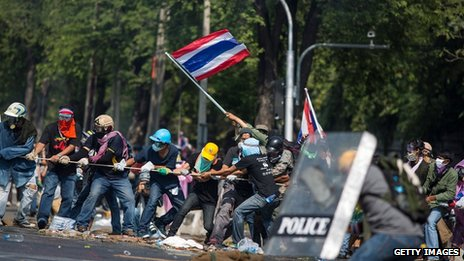 Anti-government protesters remove part of a barricade as they attempt to occupy the government house on 2 December 2013 in Bangkok, Thailand