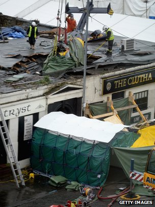 Rescuers lift the police helicopter wreckage from the roof of the The Clutha Pub