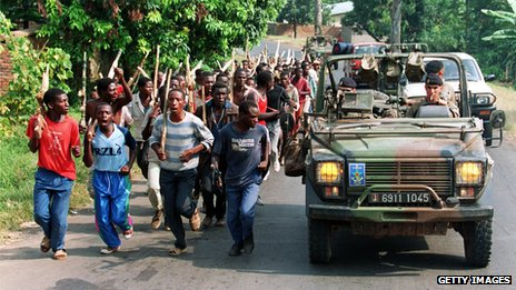 This file picture taken 27 June 1994 shows French soldiers on patrol passing ethnic Hutu troops from the Rwandan government forces, near Gisenyie