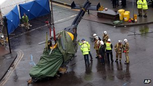 Scottish Fire and Rescue services watch as the police helicopter is lowered to the ground