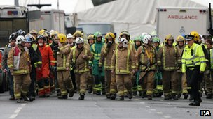 Emergency workers make their way to form a Guard of Honour salute for one of the victims
