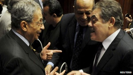 Amr Moussa (left) speaks to al-Sayed al-Badawi (right) in the Shura Council building in Cairo (1 December 2013)