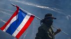 An anti-government protester carries a Thai national flag as he walk away from teargas during clashes with the police the metropolitan police headquarters in Bangkok, 2 December 2013