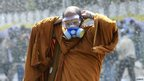 A Thai Buddhist monk puts on a gas mask as riot police use water cannon and tear gas while anti-government protesters attempt to remove barricades outside Government House in Bangkok, 2 December 2013