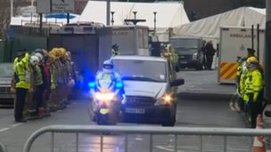 Emergency services personnel salute the cortege of private ambulances