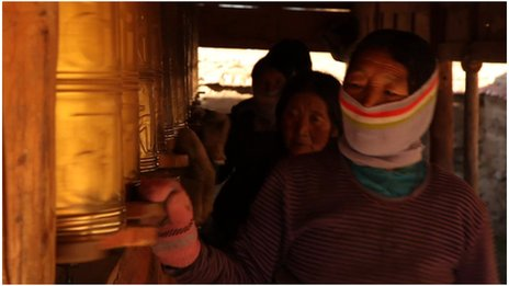 Tibetan women spin prayer wheels
