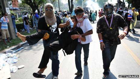Men carry a fellow protester with a rubber bullet wound during a violent anti-government protest near Government House on 2 December 2013 in Bangkok, Thailand