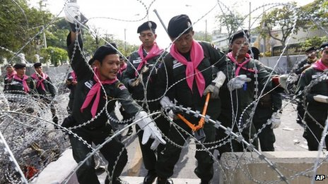 Thai police remove barbed wire outside the city police headquarters in Bangkok on 3 December 2013