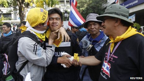 An anti-government protester kisses a riot police officer on the cheek during a rally outside the Government House in Bangkok on 3 December 2013