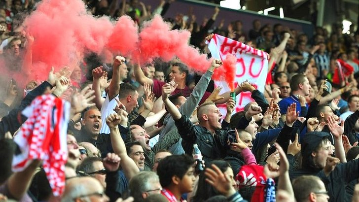 Manchester United fans light a flare during their team's match at West Brom in May 2013