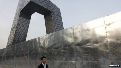 A man walks outside a construction site, next to the China Central Television (CCTV) building in Beijing's central business district, 14 April 2013