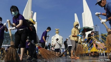 Anti-government protesters sweep the street around the Democracy Monument after weeks of protesting and days of clashes with police in Bangkok's city centre, 4 December 2013
