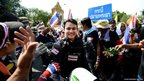 Thai riot police smile as they are cheered by anti-government protesters