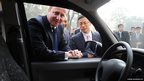 British Prime Minister David Cameron looks at a London black cab with Geely Chairman Li Shufu who intends to operate London taxis in Shanghai