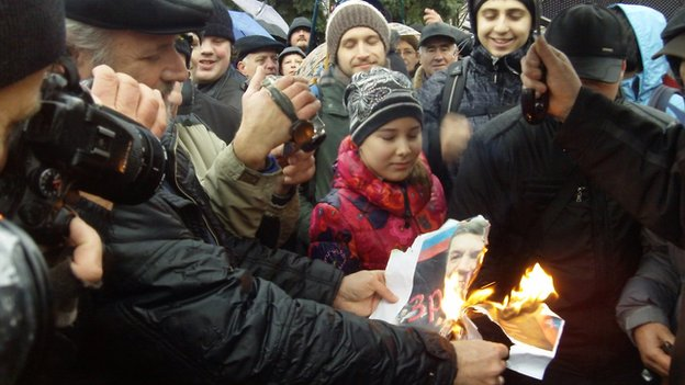 Protesters in Donetsk set fire to a picture of President Yanukovych