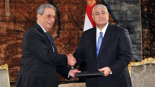 Amr Moussa (left), chairman of the constituent assembly, presents a copy of the draft constitution to interim President Adly Mansour (3 December 2013)