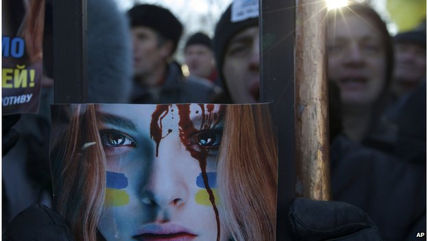 Protestors hold a poster outside the parliament building in Kiev