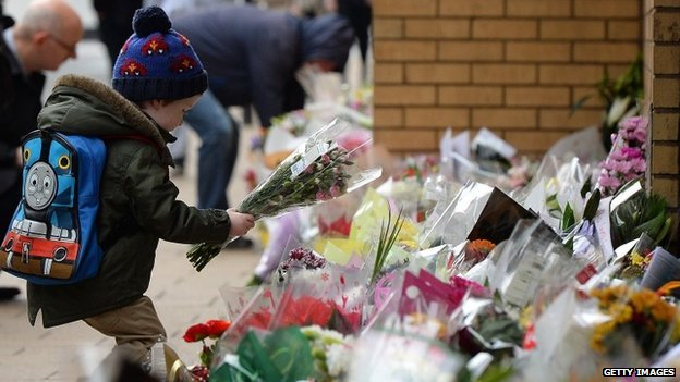 Boy lays floral tribute at scene