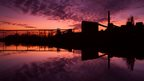 A purple and pink cloudy sky overlooks silhouetted industrial buildings and water.