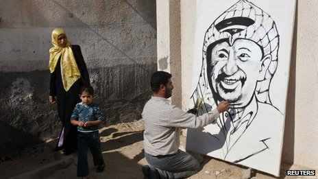 A Palestinian artist works on a mural depicting late Palestinian leader Yasser Arafat
